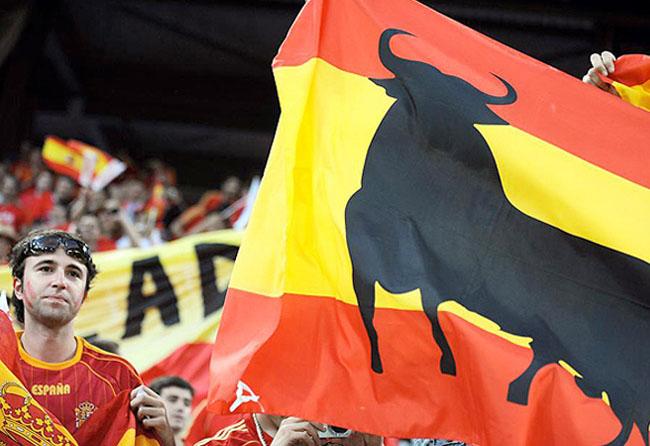 Bandera españa con aficionado futbolista y toro Osborne en el centro de la misma