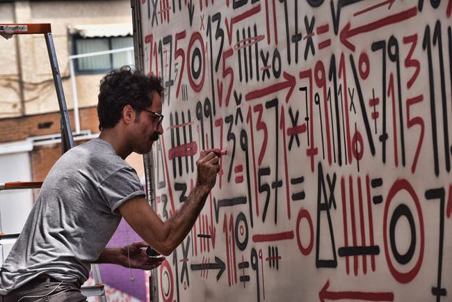 El artista Sixeart trabajando en un graffiti